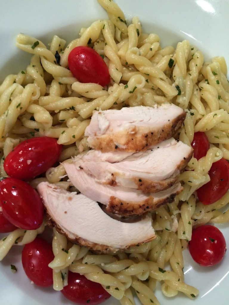 Rotisserie chicken served over gemelli pasta with pesto sauce and tomatoes